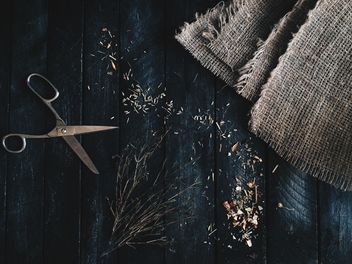 Scissors, burlap and dry herbs on dark wooden background - image #136341 gratis
