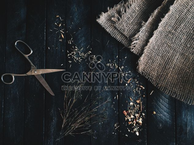 Scissors, burlap and dry herbs on dark wooden background - Free image #136341