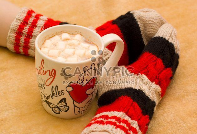 Taza de cacao y los pies en calcetines calientes - image #182561 gratis