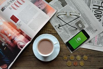 Cup of coffee, daily press and smartphone with Clashot logo on the table - image #182811 gratis