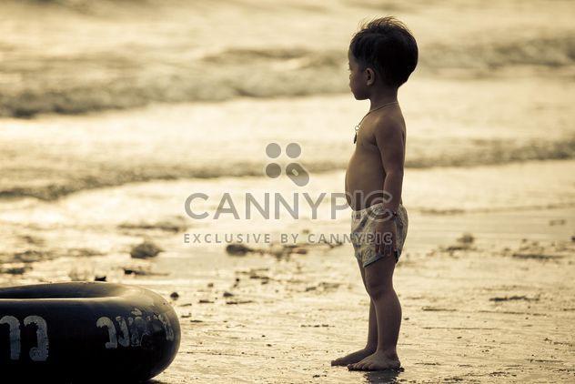 Petit garçon asiatique au bord de mer au coucher du soleil - image gratuit #183851