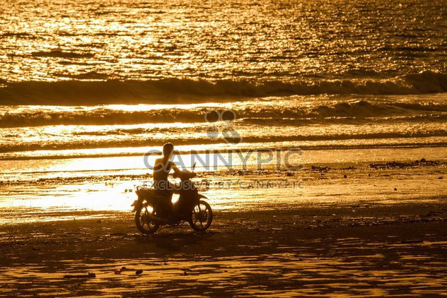 Motorcyclist drinig along a beach - Free image #183861