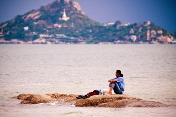 Lonely man sitting on rocks - image #185641 gratis