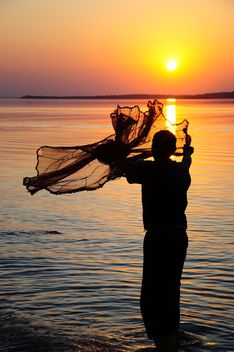 a fisherman throwing net through the sea sunset sun sundown sea man fisherman net dusk people yellow fishin - Free image #185771