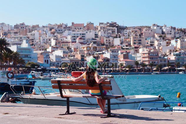 Jeune fille assise sur la digue de mer, l'île de Crète - image gratuit #186711