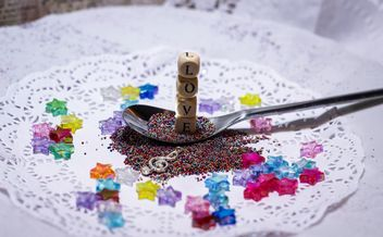 colored sequins in a spoon and a plate - image gratuit #187401
