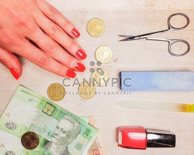 Mano mujer, dinero y accesorios para la manicura sobre fondo de madera - image #198961 gratis