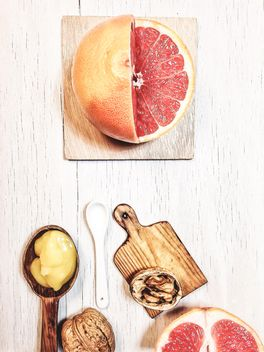 Grapefruit, walnuts and cutting board - image #199001 gratis