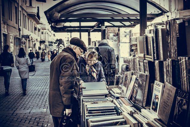 Personas mayores cerca de contador con libros en la calle - image #200761 gratis
