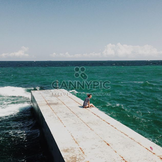 girl sitting on a wooden pier near the sea - Free image #273801