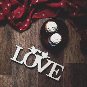 Cupcakes and word love on wooden background - Free image #273891