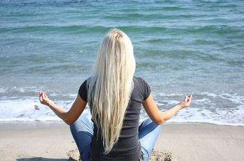 Blond girl meditating on a beach - image #273941 gratis