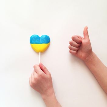 Child's hands and lollipop in colors of Ukrainian flag on white background - бесплатный image #329301