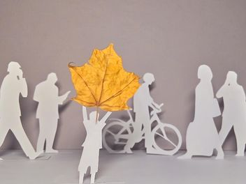 papercut people and yellow maple leaf - бесплатный image #330351