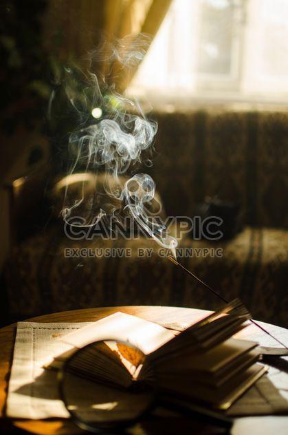 Желтые осенние листья через увеличительное стекло и палочки благовоний и книги - бесплатный image #330401