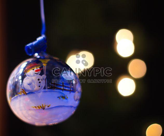 Cerca de la bola del árbol de Navidad con un muñeco de nieve - image #341541 gratis