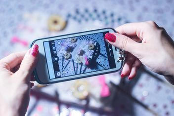 Smartphone decorated with tinsel in woman hands - бесплатный image #342181