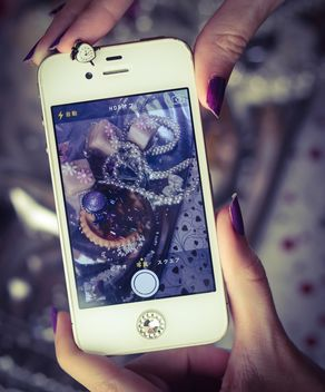 Smartphone decorated with tinsel in woman hands - бесплатный image #342191