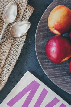 Still life of apples on a plate, two spoons and magazine - бесплатный image #342591
