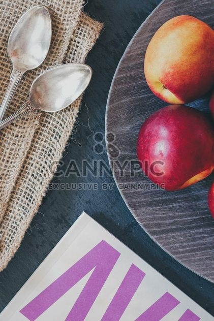 Still life of apples on a plate, two spoons and magazine - Free image #342591
