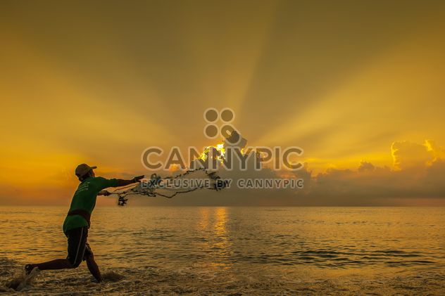 Fisherman throwing a net at sunset - Free image #344091