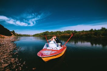 Happy wedding couple in boat on lake - бесплатный image #345111
