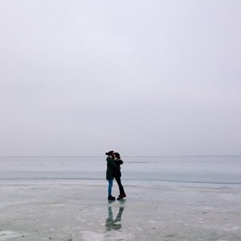 Happy couple hugging on frozen lake - бесплатный image #347171