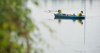 Fisherman in fishing boat on river - image #347281 gratis