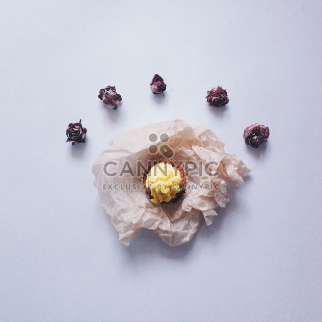 Small cupcake and dry rose buds on white background - Free image #347741