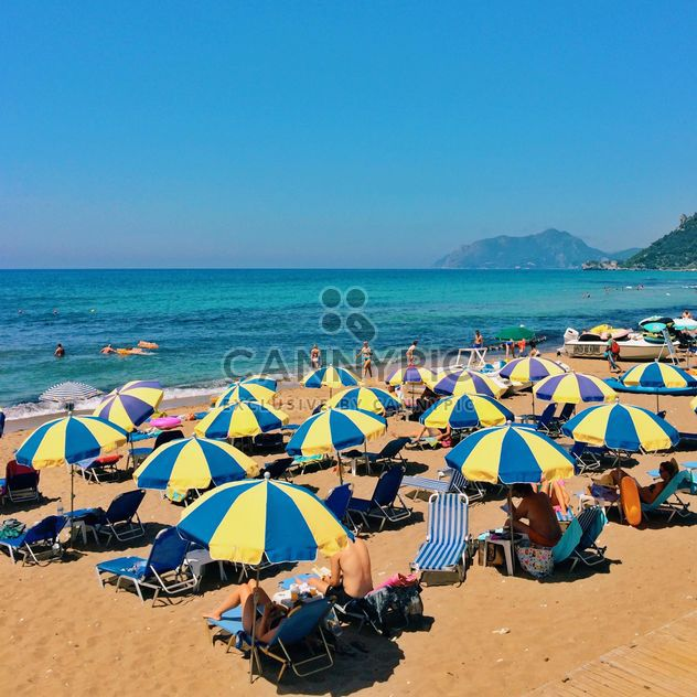 Menschen unter Sonnenschirmen am Strand - Free image #363661