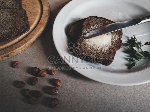 Pequeno-almoço. pão e manteiga em um prato e pão picado em uma placa de madeira - Free image #373531