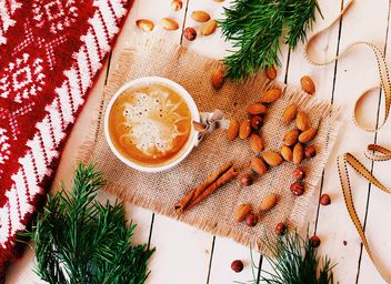 Cup of coffee, nuts and cinnamon on sacking - бесплатный image #136241