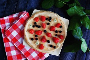 Pancakes with berries, checkered dishcloth and plant - image gratuit #136461