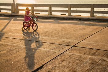 Girl riding bicycle at sunset - image #183961 gratis