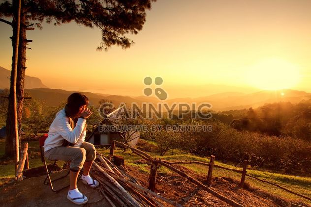 Woman watching sunset with a cup of warn drink - image #184271 gratis