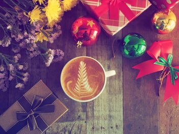 Cup of latte art with Christmas gifts on wooden background - бесплатный image #187041