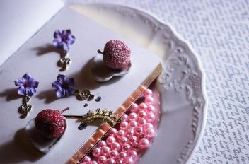 pink beads in plate and jewelry on it - бесплатный image #187281