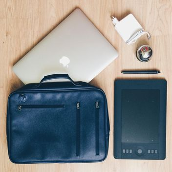 Macbook, tablet PC and designer's bag on wooden background - image gratuit #271731