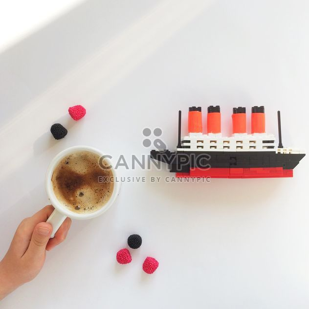 Cup of coffee, blackberries and toy ship on white background - бесплатный image #329161