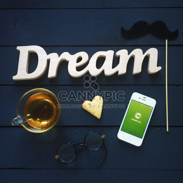 Cup of tea, smartphone with Clashot logo and accessories on dark wooden background - Free image #329311
