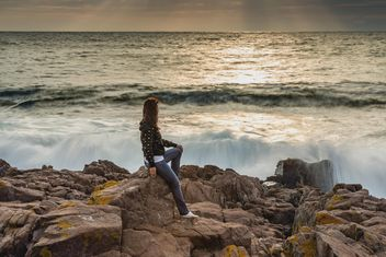 Woman sitting on rock in sea - image #338601 gratis