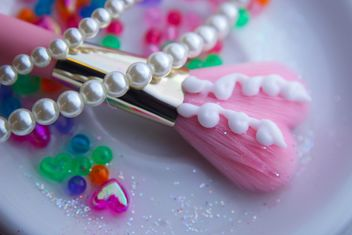 Pink makeup brush and pearls on a plate - бесплатный image #341501