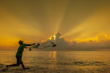 Fisherman throwing a net at sunset - бесплатный image #344091