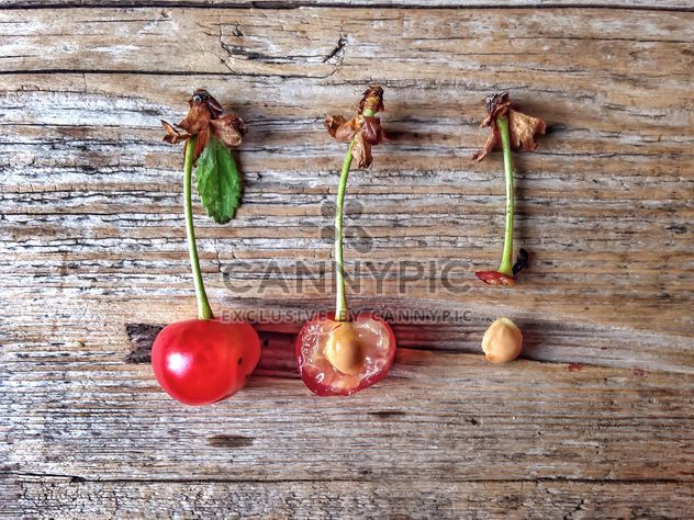Cherries and bones on wooden background - image gratuit #344571