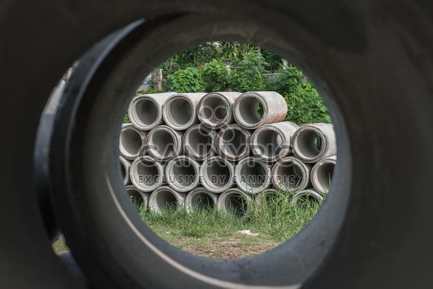 Concrete drainage pipes stacked on grass - Free image #344581