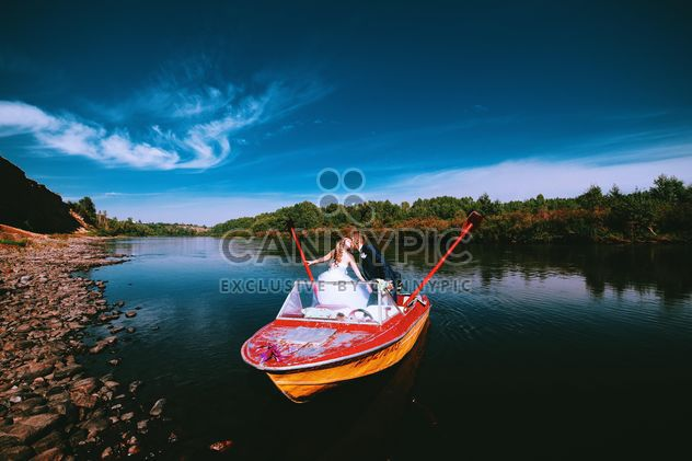 Happy wedding couple in boat on lake - image #345111 gratis
