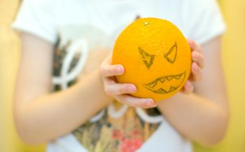 Angry orange for Halloween in child's hands - image #348011 gratis