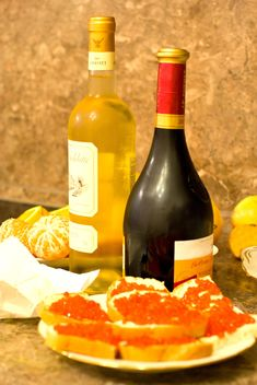 Sandwiches with red caviar and bottles of wine - бесплатный image #348031