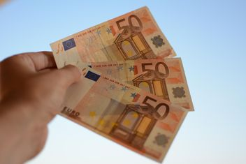 Euro banknotes in hand on blue background - image #348421 gratis