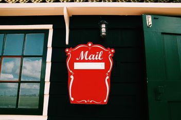 Red mail box on wall of house - image #348651 gratis